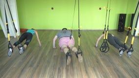 Η άσκηση ομάδας στην αρθρωμένη γυμναστική TRX όπου οι άνθρωποι κάνουν την ώθηση αρθρώνει επάνω την άσκηση, μεταβολική, γυμνάσιο απόθεμα βίντεο