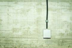 Η άσπρη έξοδος ηλεκτρικής δύναμης με την κάλυψη ΚΑΠ και το μαύρο καλώδιο σύνδεσε στο συμπαγή τοίχο grunge Στοκ εικόνα με δικαίωμα ελεύθερης χρήσης