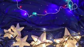 Η άσπρη γιρλάντα αστεριών βρίσκεται σε ένα μπλε υπόβαθρο φιλμ μικρού μήκους