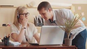 Η άσπρη θηλυκή εργασία χειριστών τηλεφωνικών κέντρων σε έναν υπολογιστή και τους περιπάτους επάνω στο διευθυντή της και επικοινων απόθεμα βίντεο