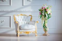 Η άσπρη καρέκλα ύφους δέρματος εκλεκτής ποιότητας στο κλασσικό εσωτερικό δωμάτιο με το μεγάλα παράθυρο και το ελατήριο ανθίζει Στοκ Φωτογραφία