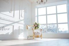 Η άσπρη καρέκλα ύφους δέρματος εκλεκτής ποιότητας στο κλασσικό εσωτερικό δωμάτιο με το μεγάλα παράθυρο και το ελατήριο ανθίζει στοκ εικόνα με δικαίωμα ελεύθερης χρήσης