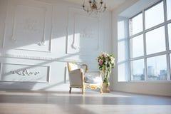 Η άσπρη καρέκλα ύφους δέρματος εκλεκτής ποιότητας στο κλασσικό εσωτερικό δωμάτιο με το μεγάλα παράθυρο και το ελατήριο ανθίζει στοκ εικόνες