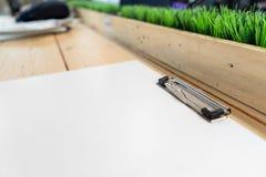 Η άσπρη κενή πλαστική περιοχή αποκομμάτων βάζει στον ξύλινο πίνακα στοκ εικόνα