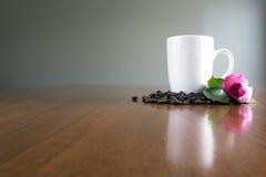 Η άσπρη κούπα με τα φασόλια καφέ και ρόδινος αυξήθηκε Στοκ Εικόνα