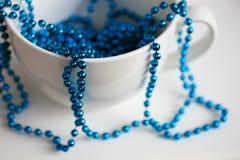 Η άσπρη κούπα με τις μπλε χάντρες στοκ εικόνα