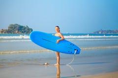 Η άσπρη ξανθή ιστιοσανίδα εκμετάλλευσης κοριτσιών surfer πηγαίνει στη θάλασσα Στοκ Φωτογραφία
