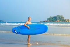 Η άσπρη ξανθή ιστιοσανίδα εκμετάλλευσης κοριτσιών surfer πηγαίνει στη θάλασσα Στοκ εικόνα με δικαίωμα ελεύθερης χρήσης