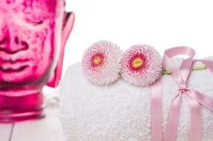 Η άσπρη πετσέτα με τα λουλούδια και το κεφάλι του γυαλιού Βούδας, SPA, απομόνωσε Στοκ Εικόνα