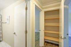 Η άσπρη πόρτα ανοίγει σε ένα οψοφυλάκιο κουζινών που γεμίζουν με τα ξύλινα ράφια στοκ εικόνες