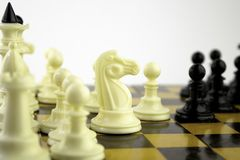 Η άσπρη στάση κομματιών σκακιού σε μια σκακιέρα κατά τη διάρκεια ενός παιχνιδιού του σκακιού, στρέφεται στο κέντρο του πίνακα στοκ εικόνα με δικαίωμα ελεύθερης χρήσης