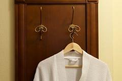 Η άσπρη υφαντική τήβεννος κρεμά στο γάντζο στην κρεβατοκάμαρα στοκ εικόνα