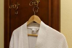 Η άσπρη υφαντική τήβεννος κρεμά στο γάντζο στην κρεβατοκάμαρα στοκ εικόνα με δικαίωμα ελεύθερης χρήσης