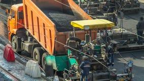 Η άσφαλτος εκφόρτωσης εκφορτωτών οπίσθιων άκρων στη μηχανή διαστολέων πεζοδρομίων στο δρόμο που επισκευάζει την οικοδόμηση λειτου απόθεμα βίντεο