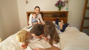 Η άτακτη οικογένεια mom με τα παιδιά αναρριχείται στον μπαμπά στο κρεβάτι Φορητός πυροβολισμός φιλμ μικρού μήκους