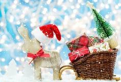 Η άλκη με το καπέλο Χριστουγέννων προσελκύει τα δώρα Χριστουγέννων Στοκ Φωτογραφίες