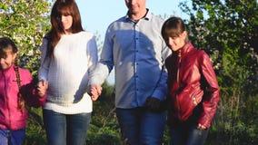 Η έγκυοι μητέρα, ο πατέρας και τα παιδιά που περπατούν άνθισαν πάρκο άνοιξη ευτυχής οικογένεια που στηρίζεται στον κήπο απόθεμα βίντεο