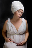 Η έγκυος γυναίκα έντυσε σε ένα τουρμπάνι και ντυμένος στο άσπρο ύφασμα Στοκ Φωτογραφία