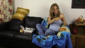 Η έγκυος γυναίκα απολαμβάνει τη γλυκιά συνεδρίαση cupcake άνετα στον καναπέ απόθεμα βίντεο