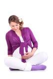 Η έγκυος γυναίκα κάθεται στο πάτωμα και κρατά την κοιλιά Στοκ εικόνες με δικαίωμα ελεύθερης χρήσης