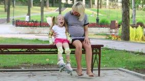 Η έγκυος γυναίκα και το μικρό κορίτσι με τα σαλάχια κυλίνδρων κάθονται στον πάγκο στο ηλιόλουστο πάρκο απόθεμα βίντεο