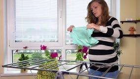Η έγκυος γυναίκα κρεμά το πλυντήριο στο σπίτι απόθεμα βίντεο
