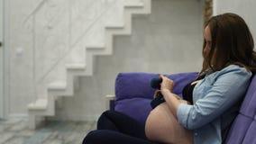 Η έγκυος γυναίκα που κάθεται στο σπίτι σε μια πολυθρόνα που παίζει τις χαριτωμένες κάλτσες μωρών στο μωρό της, αυτό έχει προτείνε απόθεμα βίντεο