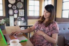 Η έγκυος γυναίκα χρησιμοποιεί το lap-top Στοκ Φωτογραφία