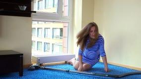 Η έγκυος καυκάσια γυναίκα χαλαρώνει στο πάτωμα και το καθαρό πάτωμα με την ηλεκτρική σκούπα απόθεμα βίντεο