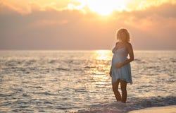 Η έγκυος όμορφη γυναίκα στέκεται στην παραλία κατά τη διάρκεια της ανατολής Στοκ Εικόνες