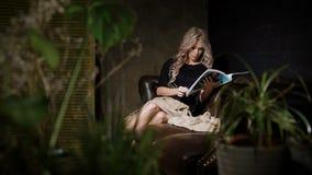 Η έγκυος όμορφη γυναίκα στο μαύρο φόρεμα χαλαρώνει στο μεγάλο καφετή καναπέ δέρματος και διαβάζει το περιοδικό αναμένων απόθεμα βίντεο
