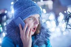 Η έκπληκτη γυναίκα που ντύνεται στα χειμερινά ενδύματα, ανοίγει το στόμα στο bewilderrment, μιλά με το φίλο της μέσω του έξυπνου  στοκ εικόνα