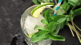 Η έκχυση στο ποτήρι πάγωσε το πράσινο τσάι με τον ασβέστη, το λεμόνι και τη μέντα στο μαύρο κατασκευασμένο υπόβαθρο απόθεμα βίντεο