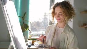 Η έμπνευση καλλιτεχνών, ταλαντούχος γυναίκα ζωγράφων αναμιγνύει τα χρώματα στην παλέτα με τη λεπτή βούρτσα εργαζόμενη στη νέα εικ φιλμ μικρού μήκους