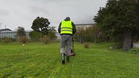 Η έναρξη εργαζομένων έκοψε τη χλόη στη βροχερή ημέρα απόθεμα βίντεο