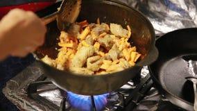 Η έναρξη να μαγειρεύει pilaf, shef ανακατώνει το κρέας με τα καρότα σε μια κατσαρόλα χυτοσιδήρων απόθεμα βίντεο