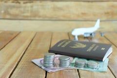 Η έννοια αποταμίευσης χρημάτων για τις διακοπές με τα νομίσματα συσσωρεύει, διαβατήριο, και παιχνίδι αεροσκαφών στα ξύλινα υπόβαθ στοκ εικόνα