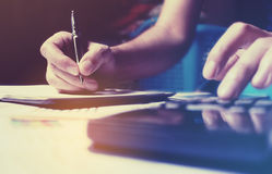 Η έννοια αποταμίευσης χρηματοδότησης με το γράψιμο χεριών γυναικών κάνει τη σημείωση και το ασβέστιο Στοκ φωτογραφίες με δικαίωμα ελεύθερης χρήσης