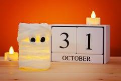 Η έννοια για αποκριές Η μούμια από το α μπορεί, γάζα και κεριά, ένα ξύλινο ημερολόγιο που παρουσιάζει στις 31 Οκτωβρίου Στοκ Φωτογραφίες