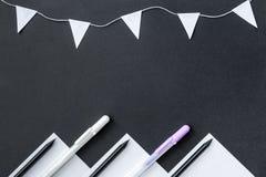 Η έννοια είναι πίσω στο σχολείο Η Λευκή Βίβλος, τα μαύρα μολύβια, οι άσπροι στυλοί και μια γιρλάντα των σημαιών βρίσκονται τυχαία στοκ φωτογραφία με δικαίωμα ελεύθερης χρήσης