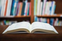 Η έννοια εκμάθησης εκπαίδευσης με το άνοιγμα κρατά ή εγχειρίδιο στην παλαιά βιβλιοθήκη, σωροί σωρών του ακαδημαϊκού αρχείου κειμέ στοκ εικόνα