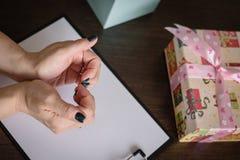 Η έννοια ενός δώρου για τις διακοπές με την αγάπη Τα χέρια των γυναικών ένωσαν σύμφωνα με την άποψη της καρδιάς, δώρα στον πίνακα στοκ φωτογραφία με δικαίωμα ελεύθερης χρήσης