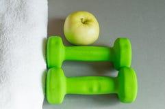 Η έννοια ενός υγιούς τρόπου ζωής, αλτήρων η πράσινη Apple και μιας άσπρης πετσέτας στο γκρίζο υπόβαθρο Στοκ Φωτογραφία