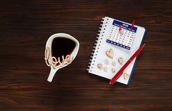 Η έννοια ημέρας βαλεντίνων ` s, το άσπρο φλυτζάνι με τον καφέ και η ξύλινη επιγραφή αγαπούν και καρδιές σε ένα σημειωματάριο με τ Στοκ Εικόνες