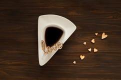Η έννοια ημέρας βαλεντίνων ` s, το άσπρο φλυτζάνι με τον καφέ και η ξύλινη επιγραφή αγαπούν και καρδιές στην ξύλινη επιφάνεια, δι Στοκ Εικόνες