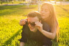 Η έννοια διασκέδασης και αγάπης με μια νεολαία συνδέει το ξάπλωμα στη χλόη και το χαμόγελο Στοκ Εικόνες