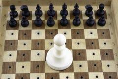 Η έννοια, μικρά μαύρα ξύλινα κομμάτια σκακιού στέκεται μπροστά από ένα μεγάλο άσπρο ενέχυρο στοκ εικόνες