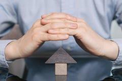 Ξύλινο σπίτι παιχνιδιών που προστατεύεται με το χέρι Η έννοια της αγοράς και της πώλησης της ακίνητης περιουσίας, κατοικία ενοικί στοκ φωτογραφίες