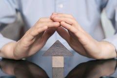 Ξύλινο σπίτι παιχνιδιών που προστατεύεται με το χέρι Η έννοια της αγοράς και της πώλησης της ακίνητης περιουσίας, κατοικία ενοικί στοκ εικόνα με δικαίωμα ελεύθερης χρήσης