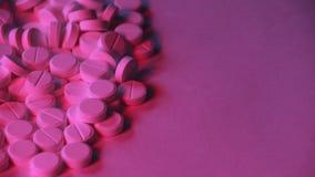 Η έννοια της εξάρτησης Πολλά άσπρα χάπια με το κόκκινος-μπλε φως νέου φιλμ μικρού μήκους